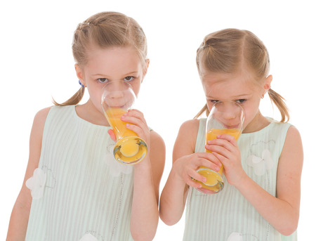 Cute sisters drink from a glass of fresh orange juice.Isolated on white background. photo