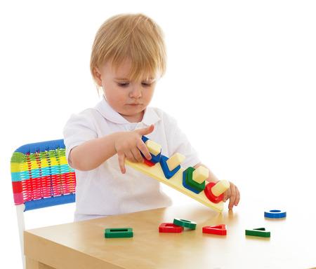 Jongetje enthousiast werken met Montessori materiaal zit aan de tafel geïsoleerd op witte achtergrond