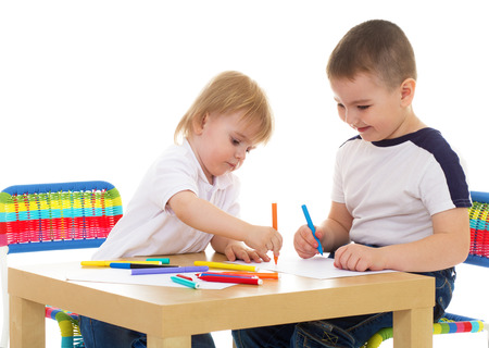 two boys enthusiastically paint markers while sitting at table  Isolated on white background  photo