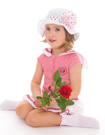 Charming little girl in sailor dress with red rose flower. The concept of a happy childhood.Isolated on white background. photo
