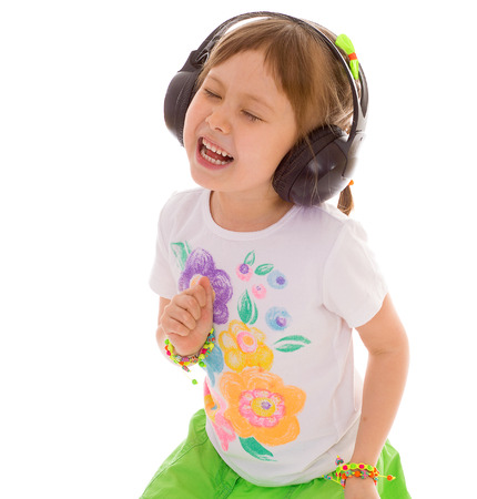 cheery: Young girl listening to music on headphones. Isolated on white background. Stock Photo