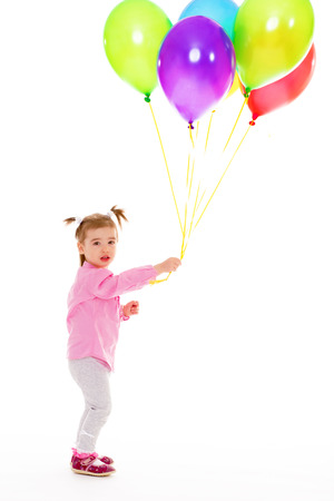 Little girl in pink shirt holding balloons photo