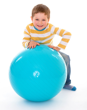 relies: Cheerful boy with a smile relies on the big blue ball, isolated on white background Stock Photo
