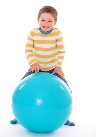 relying: Little cute boy winks, relying on the big blue ball, isolated on white background