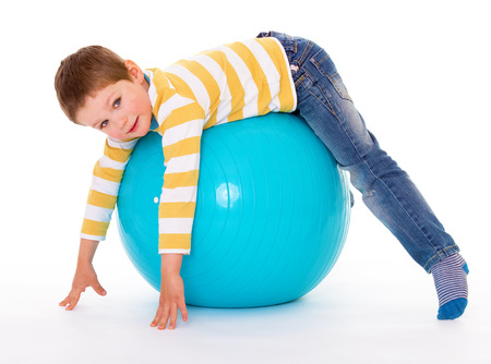 aerobic treatment: The smiling little boy lies on the big blue ball, looking at the camera, isolated on white background