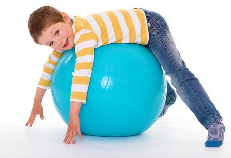 De lachende jongen ligt op zijn buik op de grote blauwe bal, geïsoleerd op een witte achtergrond