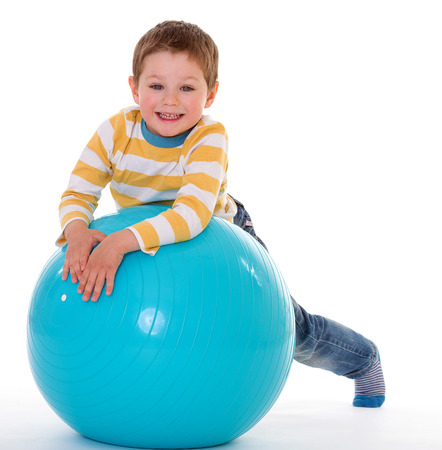 aerobic treatment: Charming little boy is based on the big blue ball, isolated on white background