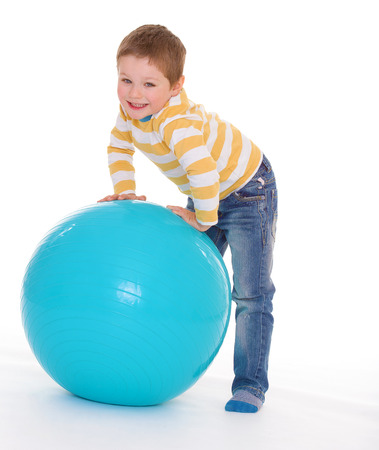 aerobic treatment: Little cute smiling boy plays with big blue ball, isolated on white background