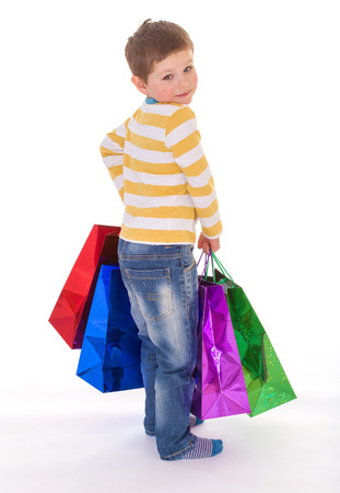 A little boy holding a colorful bags for shopping, looking back at the viewer over his shoulder, isolated on white background photo
