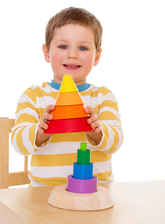 four year old: Four year old boy playing with pyramid. (Focus on the pyramid, the boys face out of focus)