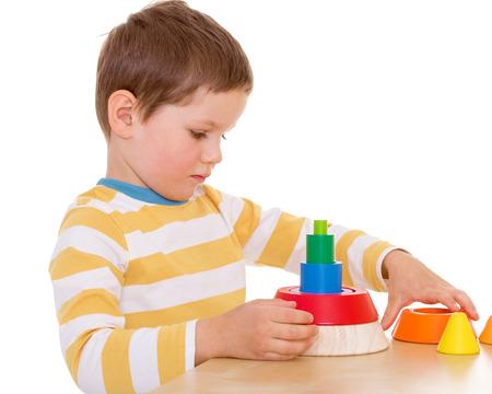 Een kleine jongen speelt met een stuk speelgoed piramide Stockfoto