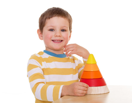 Smiling a little boy in the yellow-white striped t-shirt with a toy pyramid sits at the table photo