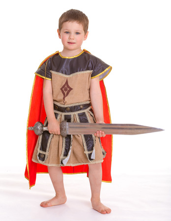 period costume: Little cute serious boy dressed as a knight, in a red cloak, with sword in hand, isolated on white background