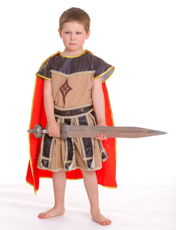period costume: Little cute serious boy dressed as a knight with a toy sword, isolated on white background Stock Photo