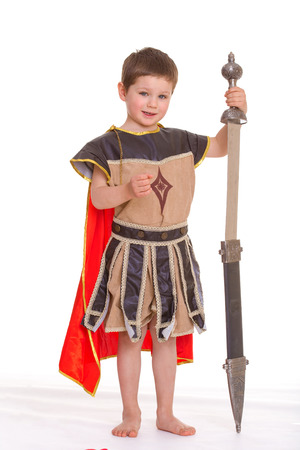 period costume: The little boy dressed as a knight is based on the sword, isolated on white background Stock Photo
