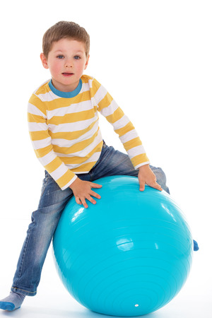 aerobic treatment: Sweet little boy sitting on a big blue ball, isolated on white background Stock Photo