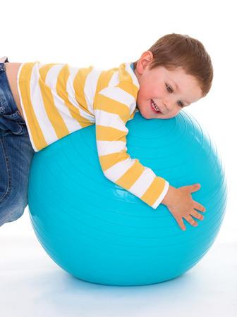 aerobic treatment: Charming little boy hugs big blue ball, isolated on white background Stock Photo