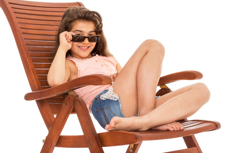 Barefoot girl in jeans shorts sitting on a wooden deck chair on white background photo