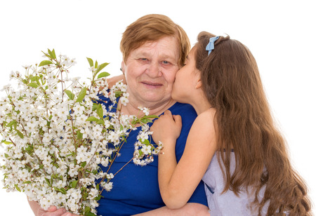 Granddaughter kisses grandmother with a bouquet of flowers photo
