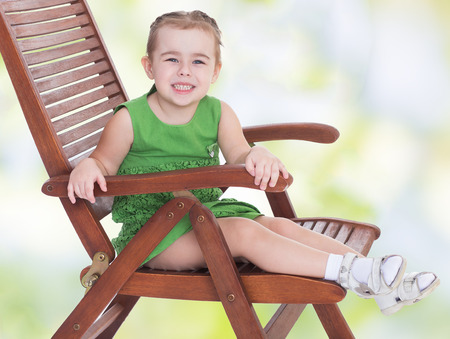 Little girl sitting on a wooden chair photo