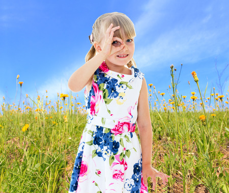 Girl looks through the fingers folded ring amid green meadows photo