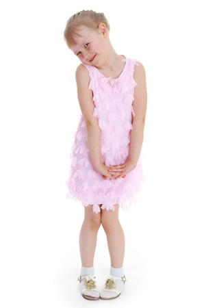 coquettish: Coquettish charming little girl in a pink dress standing on a white background