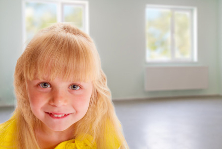 Portrait of a blonde girl in a yellow dress in an empty room photo