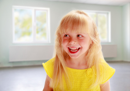 Portrait of a smiling blonde girl in a yellow dress in an empty room photo