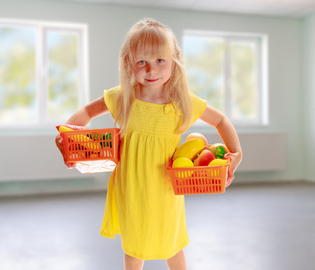 Charming blonde girl in a yellow dress holding a basket of fruit in an empty room photo