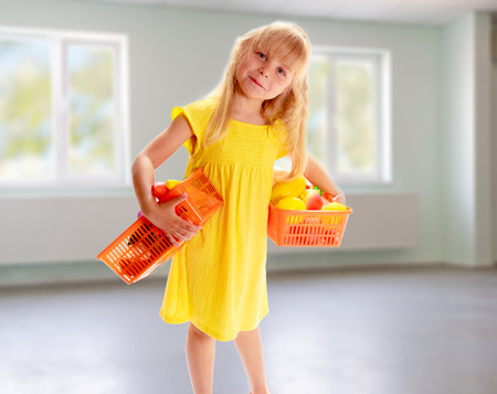 Charming blonde girl in the yellow dress is with baskets of fruit in an empty room photo