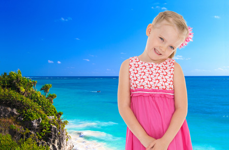 coquettish: Coquettish little fair-haired girl in a pink dress, is standing against the blue of the sea Stock Photo