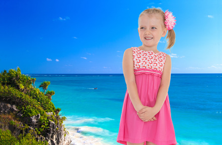 Small blonde girl in a pink dress, is standing against the blue of the sea photo