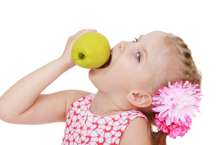 Small blonde girl bites the big yellow Apple, white background