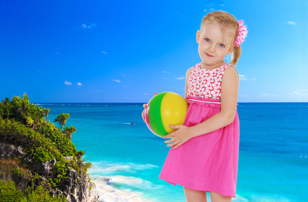 Small blonde girl standing with the ball in his hands against the blue of the sea photo