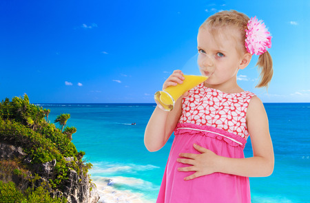 Small blonde girl is drinking juice against the blue of the sea photo