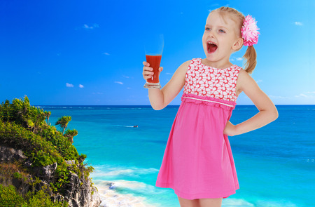 Little happy blond girl standing against the blue of the sea with a glass of juice in hand photo