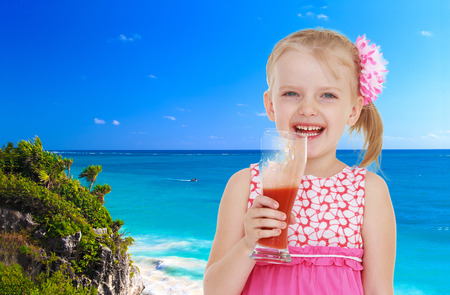 Small blonde girl standing against the blue of the sea with a glass of juice photo
