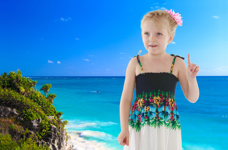 Charming little girl in the dress on the background of the ocean photo