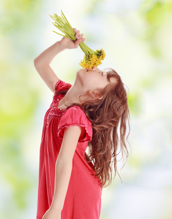 Girl smells a bouquet of yellow flowers photo