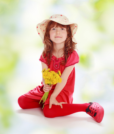 The girl in red clothes sitting with a bunch of dandelions photo
