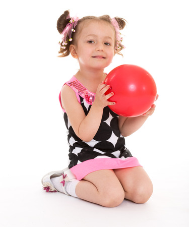 red ball in the hands of a young girl who plays them in kindergarten. isolated on white background. photo