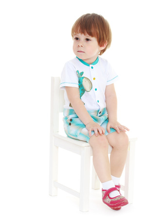 quite a little boy in a white suit, sitting on a white chair. Isolated on white background. Stock Photo