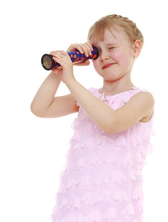 curious girl in a pink summer dress, curiously looks into a kaleidoscope. Isolated on white background