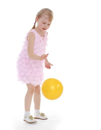 kids fun ball flies in the hands of a young girl in a pink dress. Isolated on white background photo