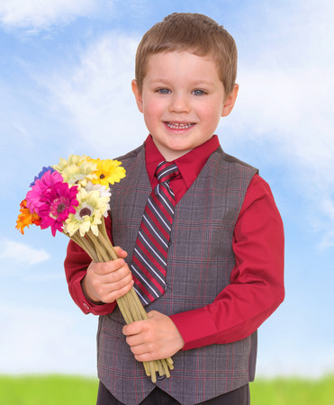 smiling little boy holding a bouquet of beautiful flowers photo