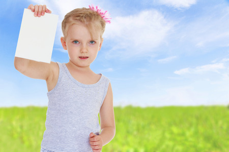 charming little girl with a white envelope in his hand on which you can write. photo
