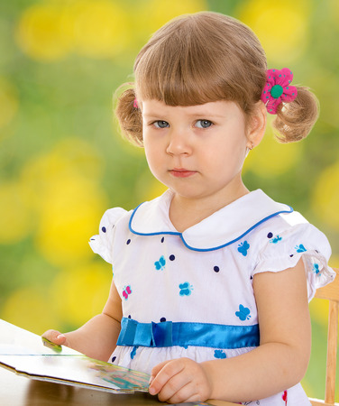 very young girl leaning on the table and looks at the camera photo