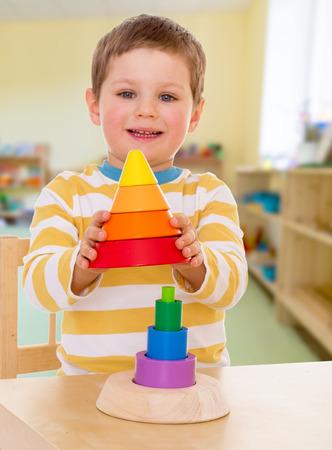 kleine jongen in de kleuterschool verzamelt kleurrijke piramide Stockfoto