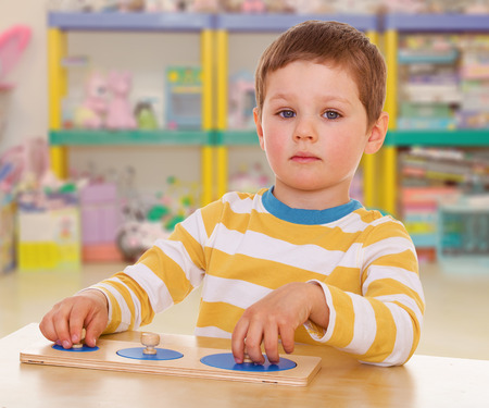 little boy collects a puzzle on a background of shelves cluttered with toys photo