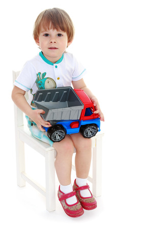 little boy sitting on a chair and holding a toy car. Isolated on background. photo